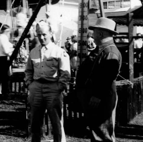 Army Pvt. Rudolph Mika (at left) of Mauston, Wis., talks to livestock buyer John Randall at the Juneau County Fair at Mauston in the summer of 1942.