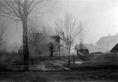 This double exposure appears to show a man walking through the remains of the fire.