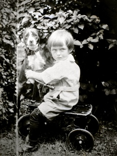 This image has a Little Rascals look and feel to it. Toddler Elaine Treutel and the family dog on her tricycle, circa 1922.