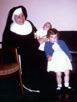 Sister Madonna Marie Mulqueen holds baby David C. Hanneman, while Laura Mulqueen Curzon looks bored.