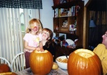 Ruby and Samantha Hanneman carve pumpkins in full face paint.