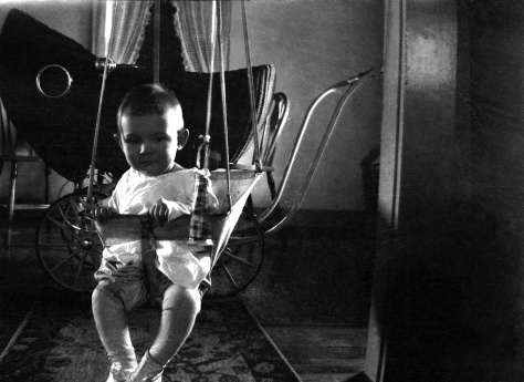 Donn Gene Hanneman, son of Carl F. Hanneman (1901-1982) and Ruby V. (Treutel) Hanneman (1904-1977), sits in an indoor baby swing at the Hanneman home in Fond du Lac, Wis, ca. 1927. Carl Hanneman was a pharmacist for the Staeben Drug Co. in Fond du Lac at the time.