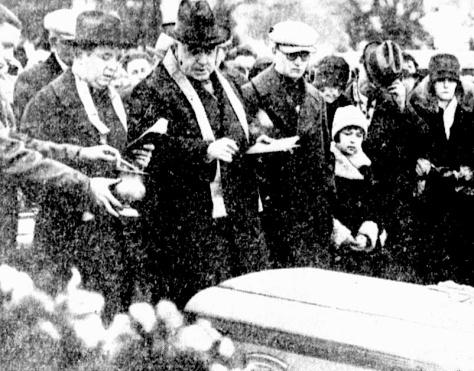 Revs. John Sullivan and John Piette of St. Mary's Catholic Church bless Helen's casket before burial.