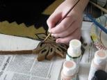 Samantha J. Hanneman retouches details on the Baby Jesus figure built by her grandfather, David. D. Hanneman.