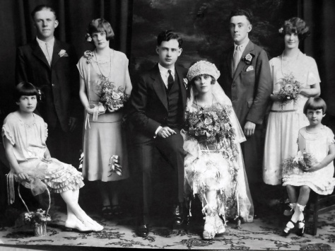 The wedding party of groom Carl Henry Frank Hanneman, 23, and Ruby Viola Treutel, 21. Wedding was July 14, 1925 at St. James Catholic Church, Vesper, Wis.  At front left is flower girl Nina Treutel, 11, sister of the bride. At front right is ring-bearer Elaine Treutel, 5, sister of the bride. Across the back, left to right, are Joe Ladick (bride's cousin), Gladys Cole (bride's cousin), groom Carl Hanneman, bride Ruby V. Hanneman, best man Wendell Miscoll, and maid of honor Esther Allbrecht.