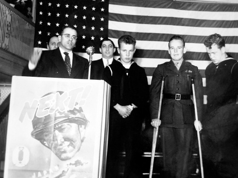 Three Mulqueen brothers appear at a Milwaukee war bond drive in November 1944. Left to right are Michael Thomas Mulqueen, Earl James Mulqueen Jr. and Patrick Joseph Mulqueen. Behind the group is war bond chairman Ben Barkin.