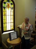 Mary K. Hanneman next to one of the window sections she and the late David D. Hanneman donated to St. Mary's Hospital.