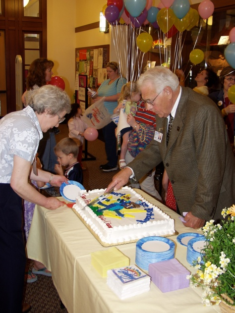 Mayor Dave Hanneman cuts the cake at the 5th birthday of the new Sun Prairie Public Library.