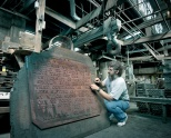 """Tom Pankratz examines what is believed to be the original wooden """"Sifting and Winnowing"""" plaque form."""