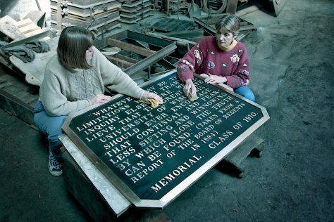 Martha Glowacki and Mary Dickey do finish work on one of the plaques.