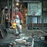 Pankratz moves the bucket of molten metal with the aid of a hoist.