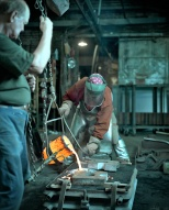 Pankratz pours molten metal into the form while Dave Olson watches.