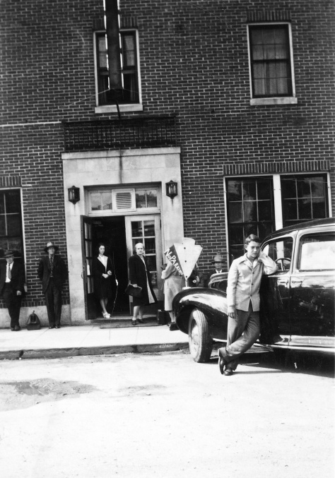 David D. Hanneman leans on the family car in front of the Ortman Hotel.
