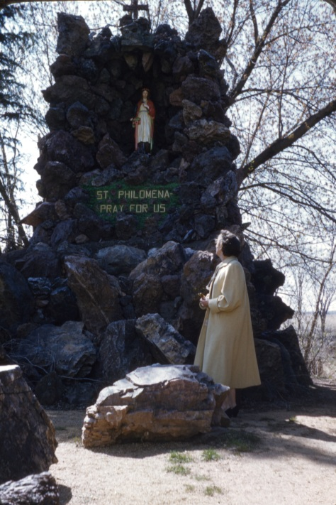 Ruby V. Hanneman stands at the St. Philomena shrine in Rudolph in the late 1950s.
