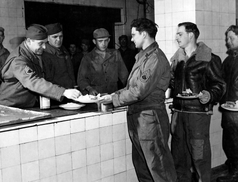 Staff Sgt. Charles D. Grinolds of Mauston (second in line) waits to be administered a sulfa pill, part of a U.S. Army Air Force effort to reduce illness at the 91st Bomb Group in England during World War II.