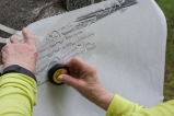 Ruth (Mulqueen) McShane does a stone rubbing of Patrick Mulqueen's monument.
