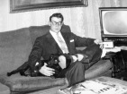 David D. Hanneman and dog Bubbles sit under the Loomis painting, circa 1950.