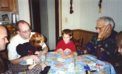 Grandpa Dave plays cards with grandchildren Samantha and Stevie Hanneman while Joe and David Hanneman look on.