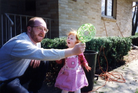 Redhead Samantha Hanneman and Dad Joe play bubbles on a spring day.