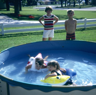 Marghi and Amy Hanneman in the pool; Laura Mulqueen and David C. Hanneman standing.